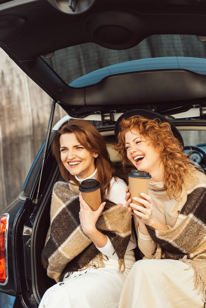 Selective focus of laughing women wrapped in blankets holding disposable coffee cups and sitting in car trunk at street