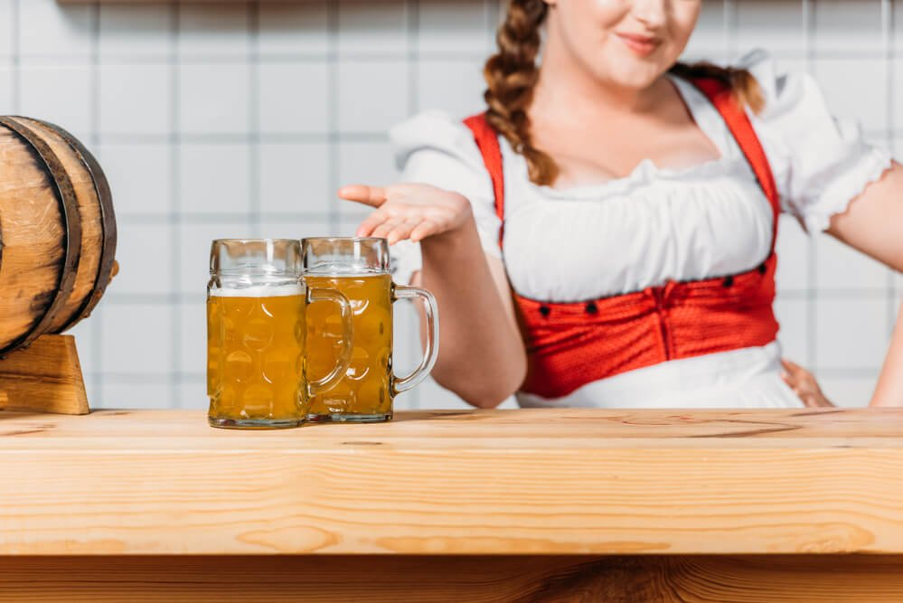 Cropped image of oktoberfest waitress in traditional bavarian dress pointing at mugs of light beer on bar counter